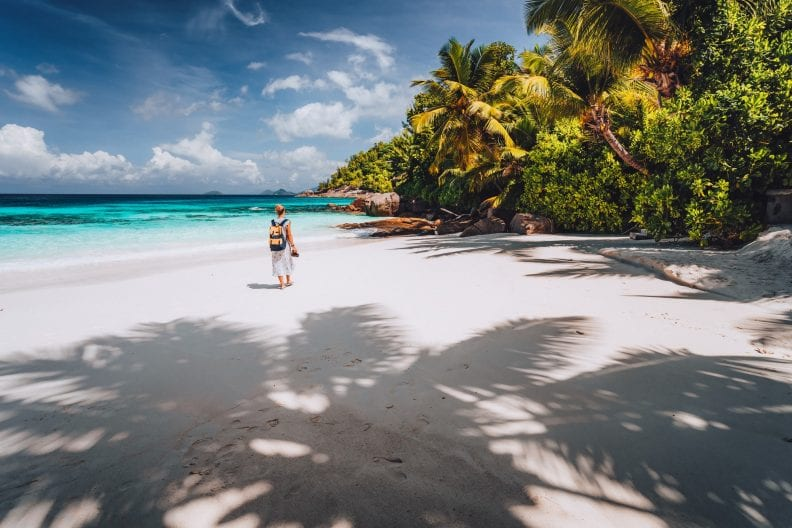 Female tourist enjoy summer vacation on tropical island. Sand beach, with shadows of palm trees and
