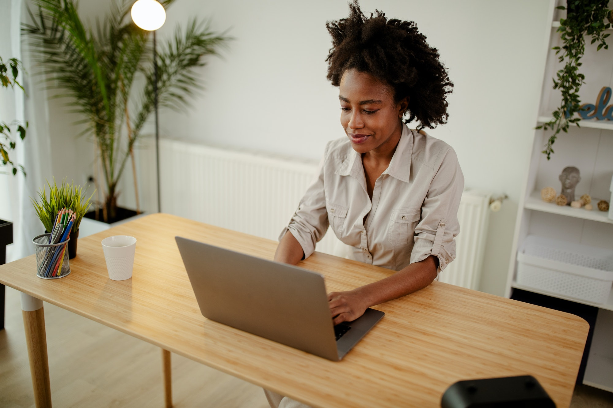 Young black smiling woman working at computer in an office.